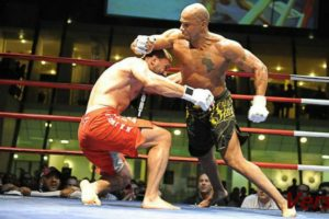 MMA activist Bacar Baldé striking opponent during an MMA match, using his boxing skills to dominate opponent