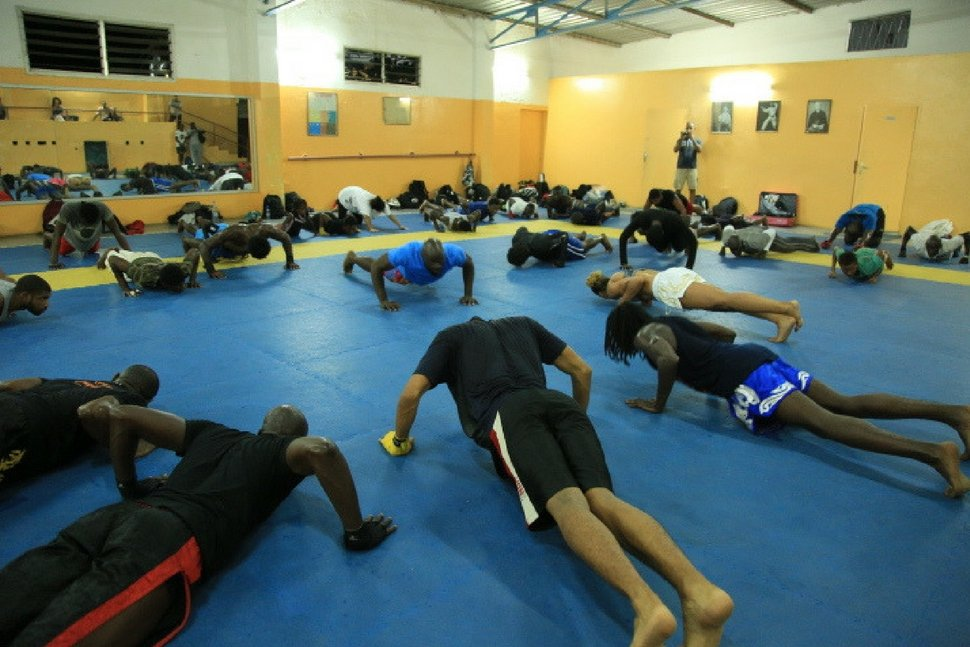 dozens of martial artist in the pushup position during muay thai warmups for class designed to develop the striking capacity of mma fighters in africa